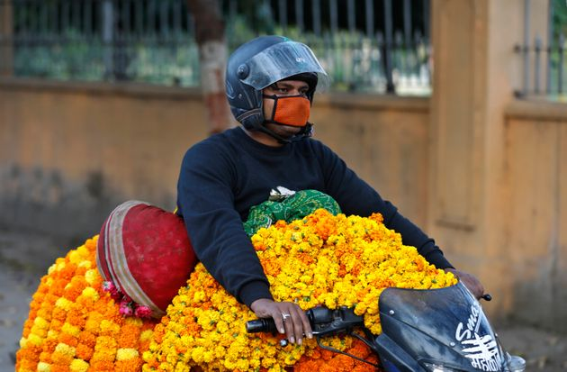 A man wearing a mask transports marigold flower garlands on a motorcycle during Navratri festival in...