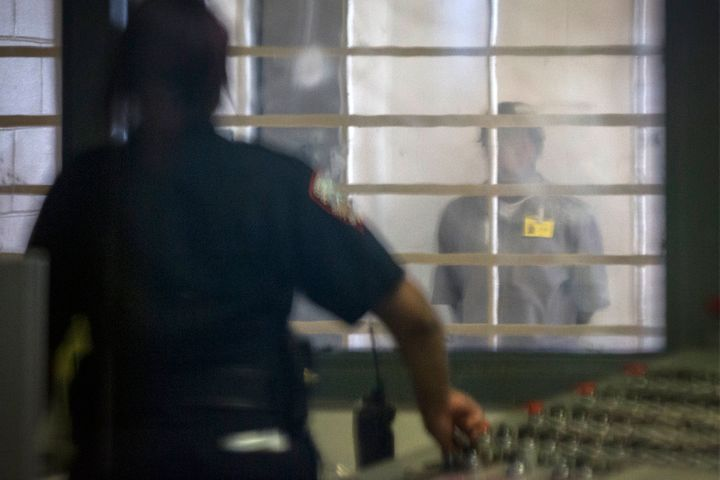 A prisoner looks at a corrections officer from behind several layers of glass and bars in the enhanced supervision housing un