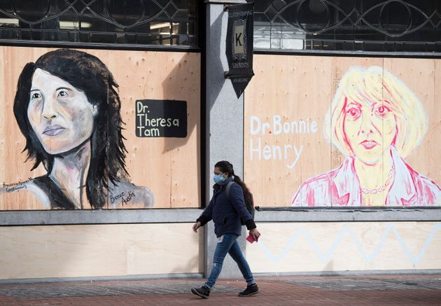 A woman wearing a protective face mask walks past portraits of Dr. Theresa Tam and Dr. Bonnie Henry on...