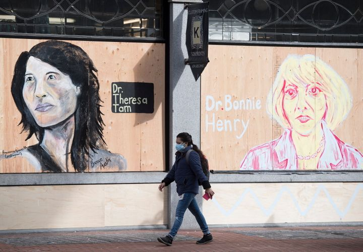 A woman wearing a protective face mask walks past portraits of Dr. Theresa Tam and Dr. Bonnie Henry on a boarded up business in downtown Vancouver, B.C. on April 1, 2020.