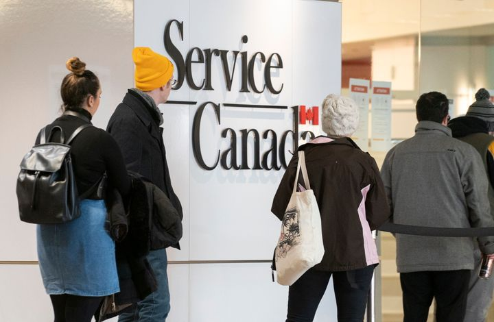 People line up at a Service Canada office in Montreal on Thursday, March 19, 2020.