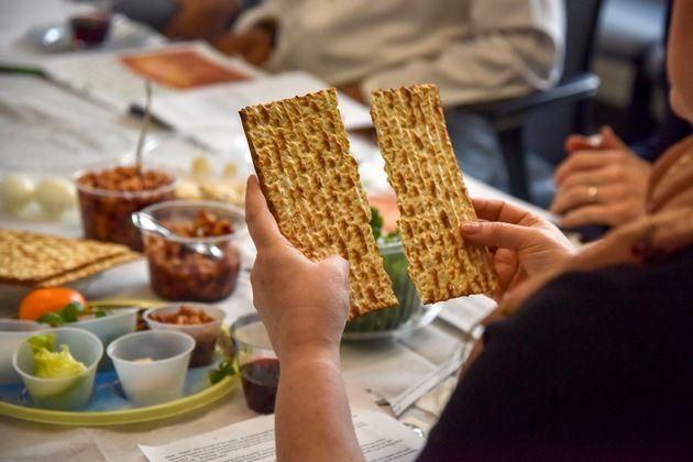 Rabbi Janet Ozur Bass breaks a piece of matzo at an Interfaith Passover seder on April 24, 2019, in Rockville,