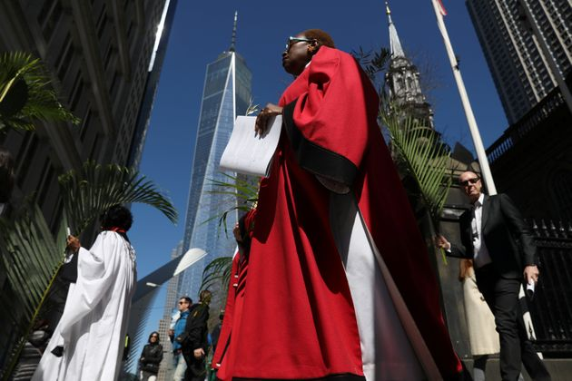 Worshippers walk with palms during a Palm Sunday procession from St. Paul's Chapel in Manhattan on April...