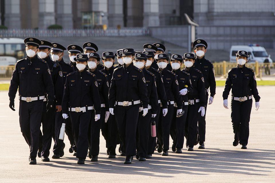Policiais chineses utilizando máscaras protetoras marcham pela Praça Tiananmen durante...