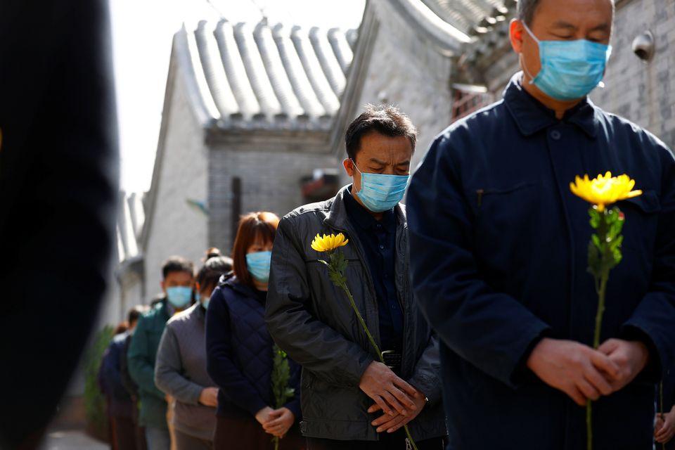 Pessoas segurando flores observam um momento de silêncio em um evento memorial em