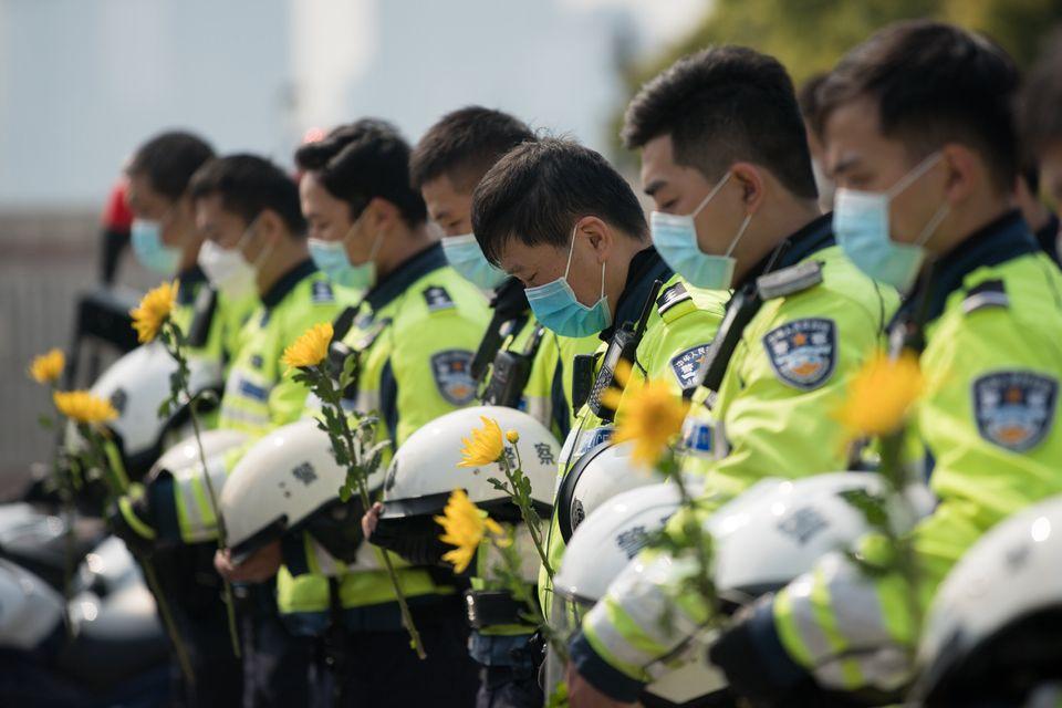 Policiais chineses usam máscaras protetoras em homenagem silenciosa durante um memorial para lamentar...