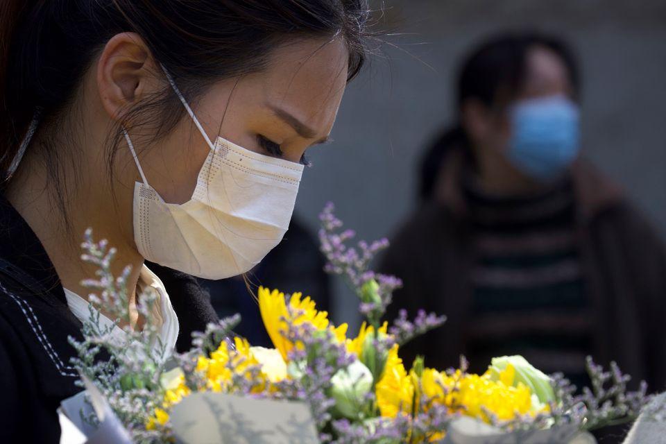 Uma mulher segura um buquê floral enquanto as pessoas se reúnem em memorial oficial realizado...
