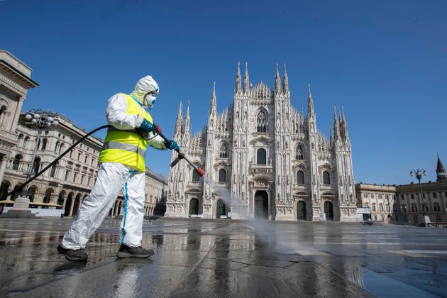 A worker sprays disinfectant to sanitize Duomo square, as the city main landmark, the gothic cathedral,...