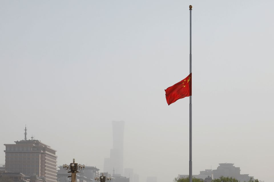 A bandeira nacional chinesa voa a meio mastro na Praça Tiananmen, em