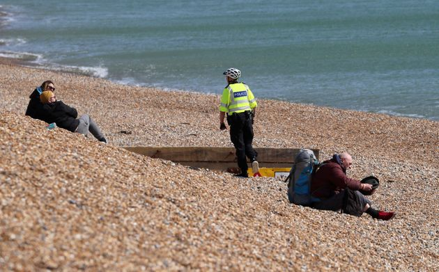 A police officer asks people to leave the beach in Brighton, south England, as the UK continues to implement...