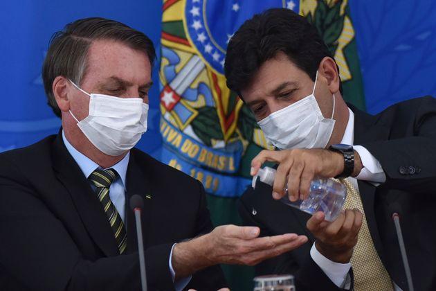 Bolsonaro (à esq.) e Luiz Henrique Mandetta passam álcool em gel durante coletiva de imprensa...