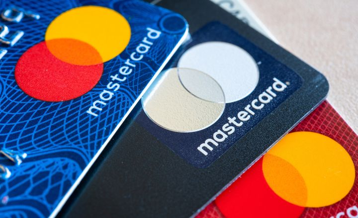 Three MasterCard credit cards of varying colours are seen in this stock photo.