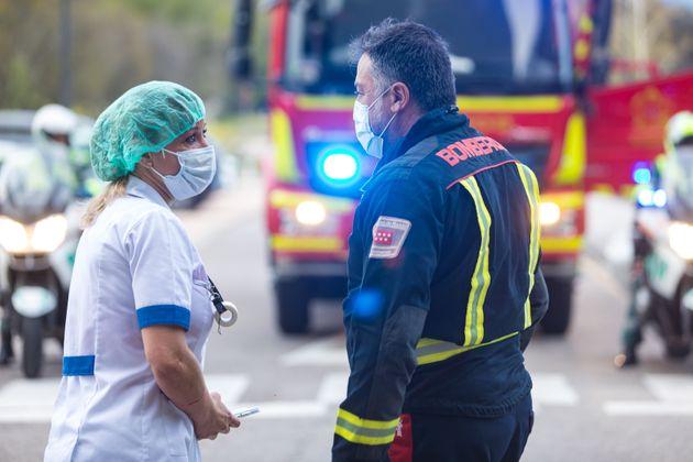 Enfermeira e bombeiro são vistos conversando do lado de fora do Hospital Geral Villalba em 5 de...