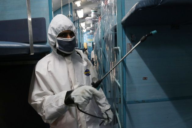 A worker in protective gear sprays disinfectant inside a train carriage converted into an isolation ward...