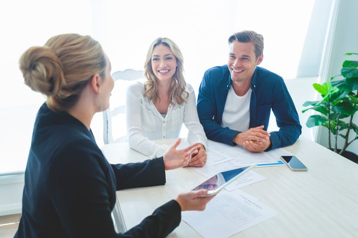 A mortgage broker sits with a young couple to go over finances in this stock image. A CMHC survey suggests nearly half of Canadians used brokers to get a mortgage in 2019.