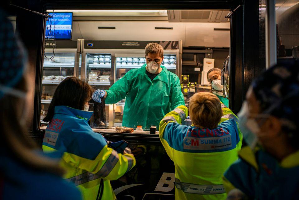 Uno de los voluntarios de Viena Capellanes ofrece comida y bebida a los sanitarios de