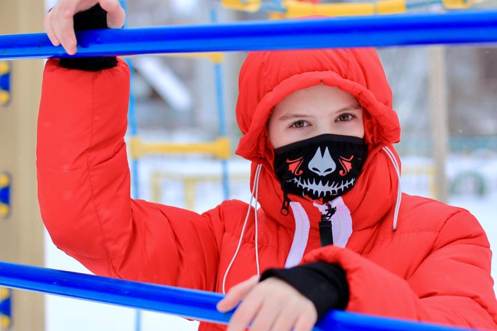 Teenage girl wearing protective color fabric bandana, mask with a trendy skull print on her face, against transmissible infectious diseases and as protection from the weather in the playground.
