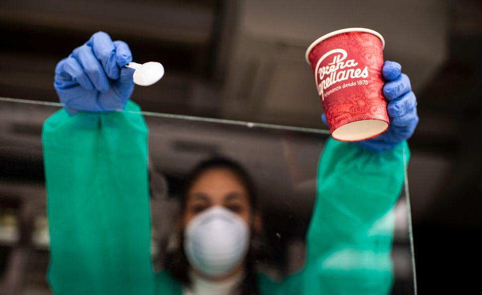 Una voluntaria ofrece café desde el autobús de Viena Capellanes en