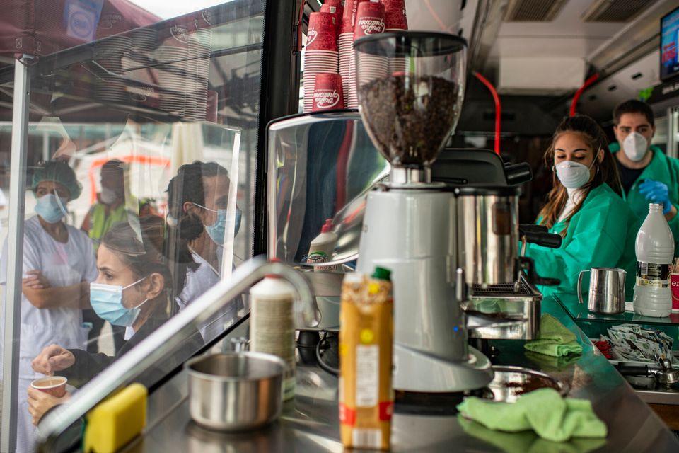 Varias personas toman el café que les ofrecen las