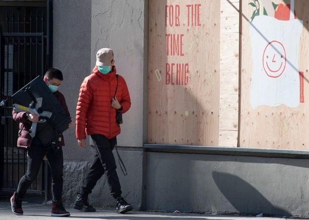 Two men wearing protective face masks as they walk past boarded up shops in downtown Vancouver in Apr....