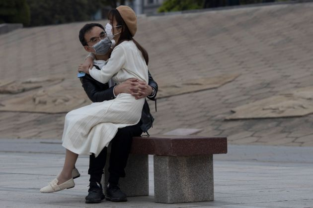 A couple wearing masks sit together on a bench as the city of Wuhan slowly loosen up ahead of a lifting...