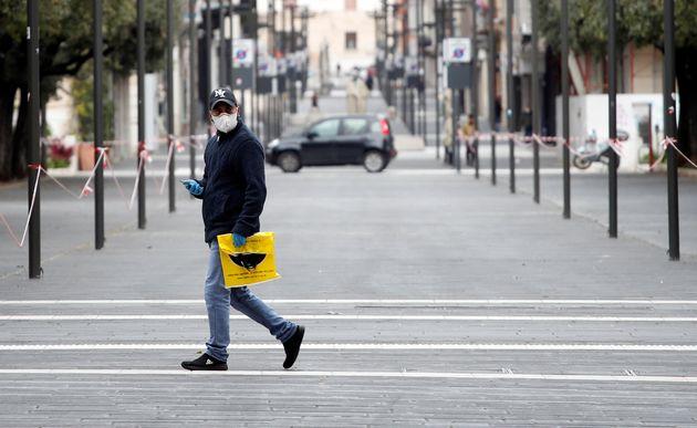 Un homme dans la rue de Bari, en Italie où parler de mettre fin au confinement dès maintenant...