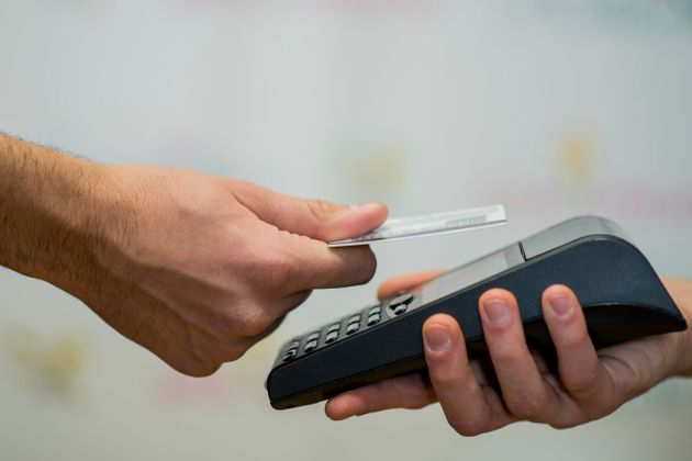 A touchless transaction is seen here in this undated stock photo. Credit card purchases cost retailers...