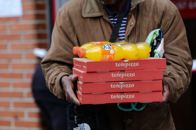 Un hombre recibe varias pizzas de Telepizza dentro del menú para familias desfavorecidas de la...