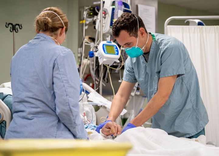 Lt. Wade Miller, from Orlando, Florida, treats a non-COVID-19 patient aboard the hospital ship USNS Mercy on Saturday.