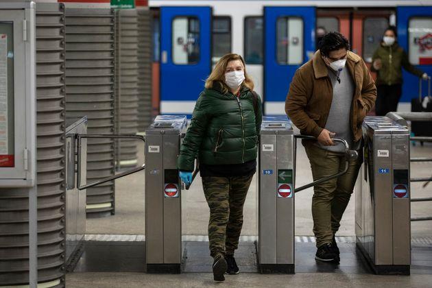 Usuarios de metro en la estación de Atocha con mascarillas para protegerse del