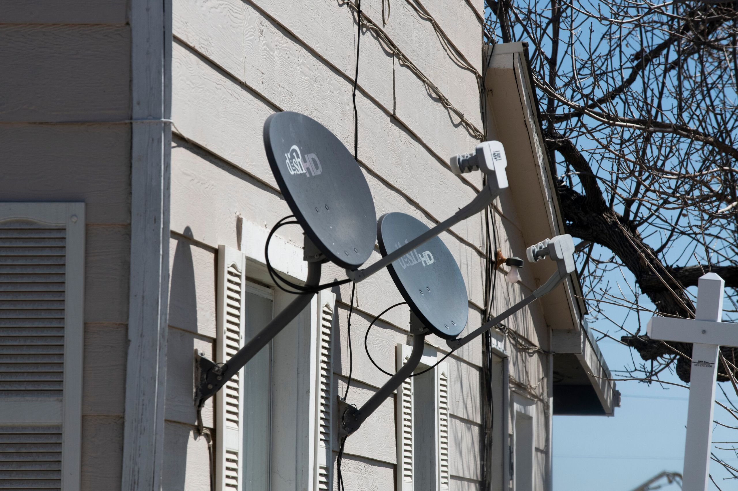 Satellite dishes for TV are shown on the side of a house in Bennett, Colorado. Many Bennett residents rely on satellite inter