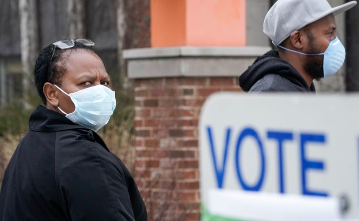 Voters masked against the coronavirus line up at Riverside High School in Milwaukee for Wisconsin's primary election on Tuesd