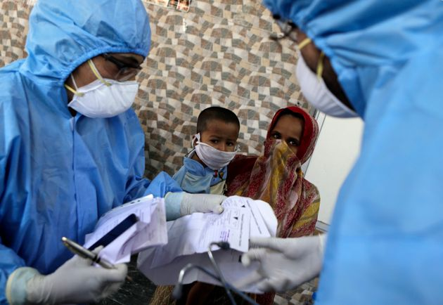 Doctors interact with people at a slum area during lockdown to control the spread of the new coronavirus...