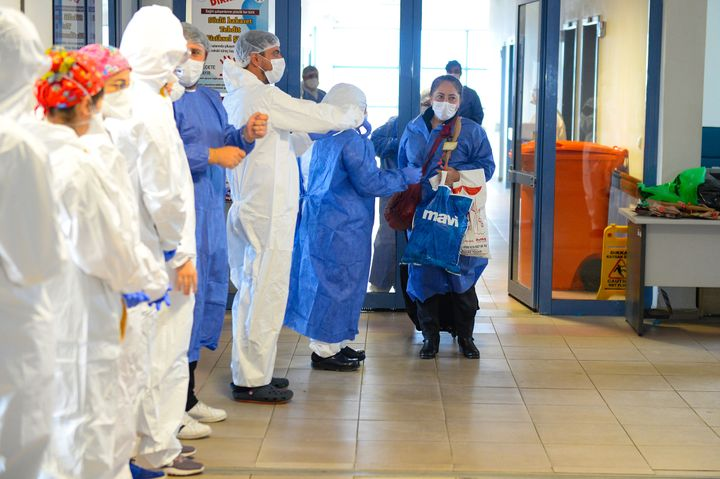 In Igdir, Turkey, doctors and nurses gather Tuesday to applaud as a COVID-19 patient is discharged from the hospital. Research has been unclear on how long a patient might remain infectious after symptoms have ended.