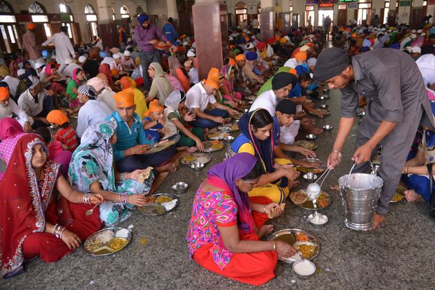 Sikh devotees eat a communal vegetarian meal, known as langar, in a hall at the Golden temple in Amritsar...