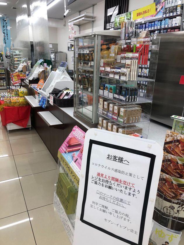 買い物の時も感染リスクはある。感染予防のため、レジにシールドを貼り、飛沫による感染を防ぐコンビニも。床に印をつけてレジ待ちの間隔をあけるよう張り紙が貼り出されていた=2020年4月6日、東京都内