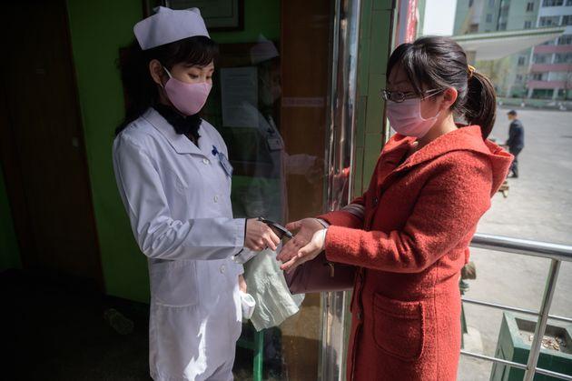 평양 시내에서 의료 관계자가 시민에게 손소독제를 뿌려주고 있다. 2020. 4.