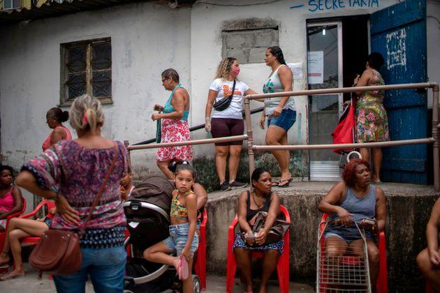 Mulheres fazem fila para receber doações de cesta básica por ONG na Cidade de Deus,...