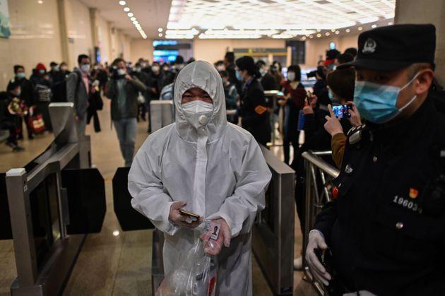 보호복을 입은 남성이 우한을 떠나기 위해 한커우 역을 통과하고 있다. 2020. 4.