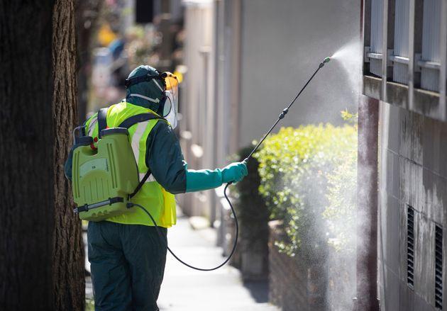 Un employé désinfecte les rues de