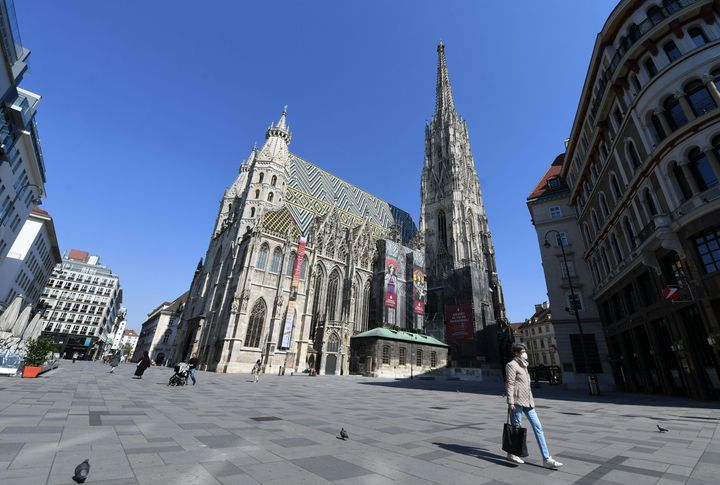 A woman with face protection mask walks past Saint Stephen's Cathedral (Stephansdom) in Vienna.