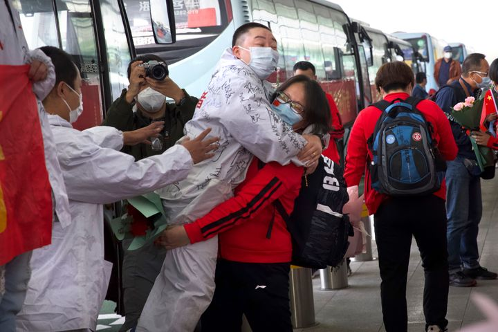 A medical worker from China's Jilin Province, in red, embraces a colleague from Wuhan as she prepares to return home at Wuhan