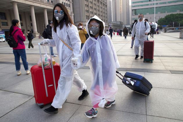 Passengers wearing face masks and raincoats to protect against the spread of new coronavirus walk outside...