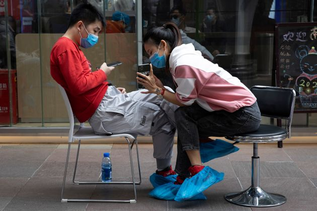 A man and woman sit together outside a blood donation center in Wuhan on Tuesday, April 7,