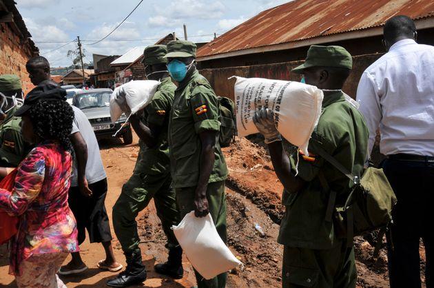 Miembros de las fuerzas armadas de Uganda distribuyen comida a gente afectada por la cuarentena para...