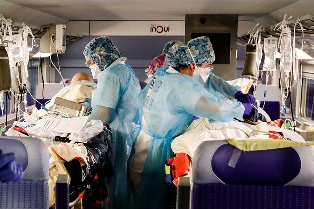 Des soignants installent des patients infectés par le COVID-19 à bord d'un TGV médicalisé à la Gare d'Austerlitz...