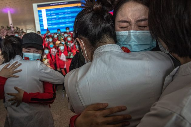Medical workers embrace one another as they prepare to leave the Chinese city of Wuhan, which was the...