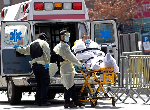 A patient is wheeled out of Elmhurst Hospital Center to a waiting ambulance in New York City on Tuesday...