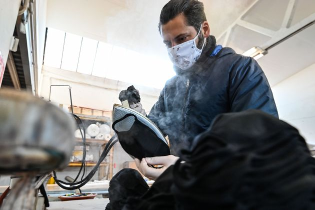 A worker sterilizes a face mask made of Nonwoven fabric (TNT Tessuto non Tessuto) with the hot steam...