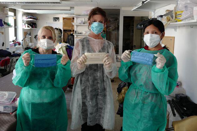 Trois couturières posent après avoir cousu une série de masques de protection contre...